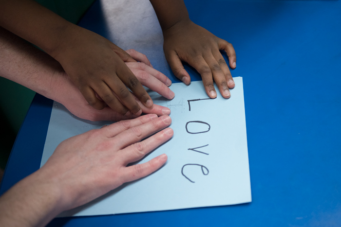 "Hands reading the word ""love"" in braille"