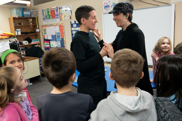 Teacher Wendy Harris greets an adult volunteer while surrounded by 2nd and 3rd grade students
