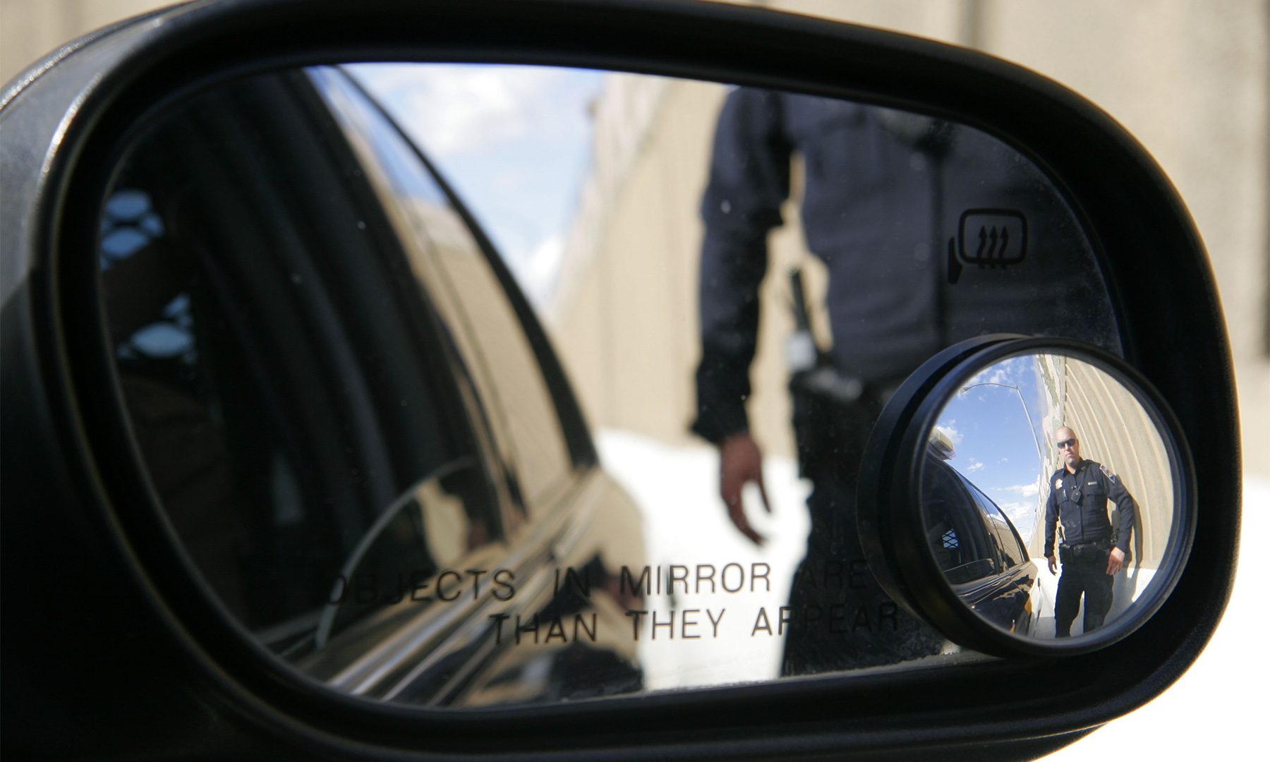 Police officer seen approaching in a car's side mirror.