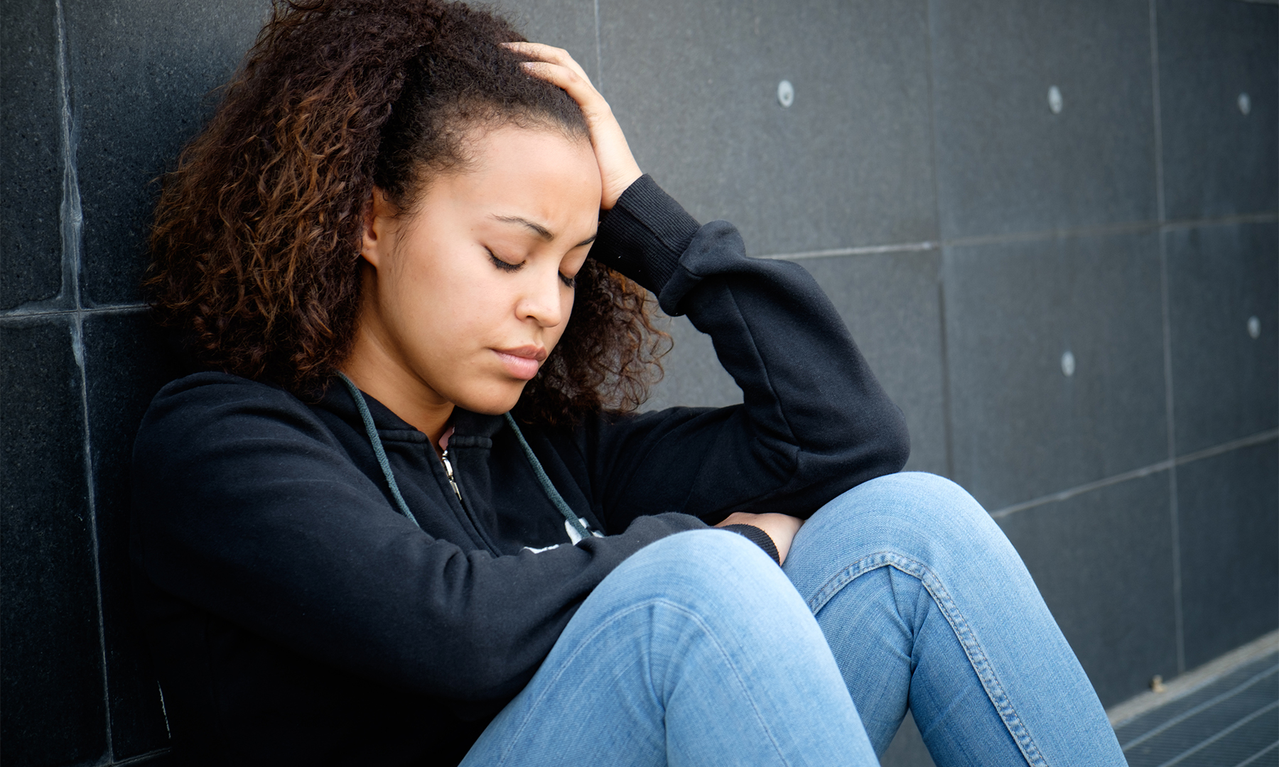 Young person of color in visible distress sitting with their back against a wall, hand on their head.
