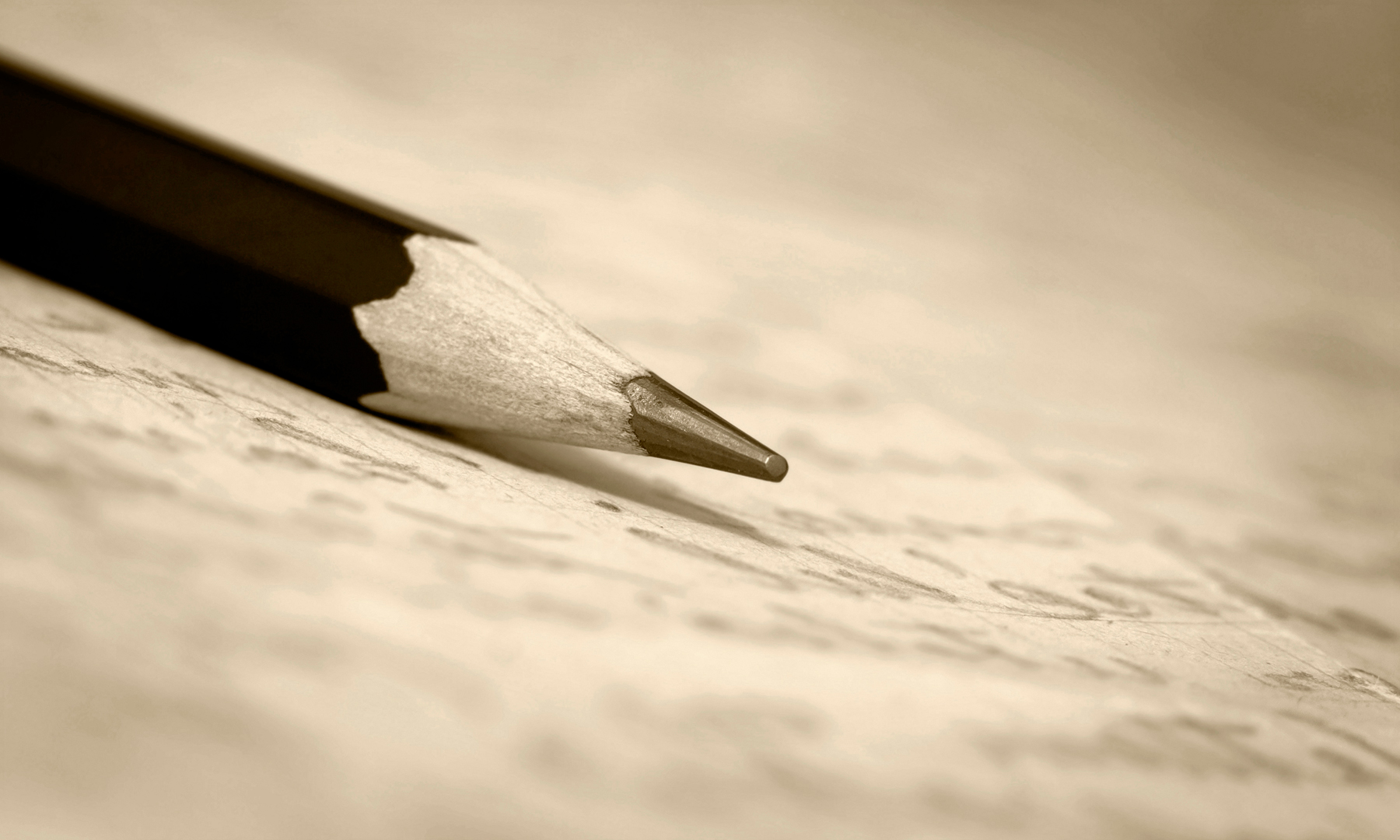 A pencil sitting on top of a sheet of paper with writing on it.