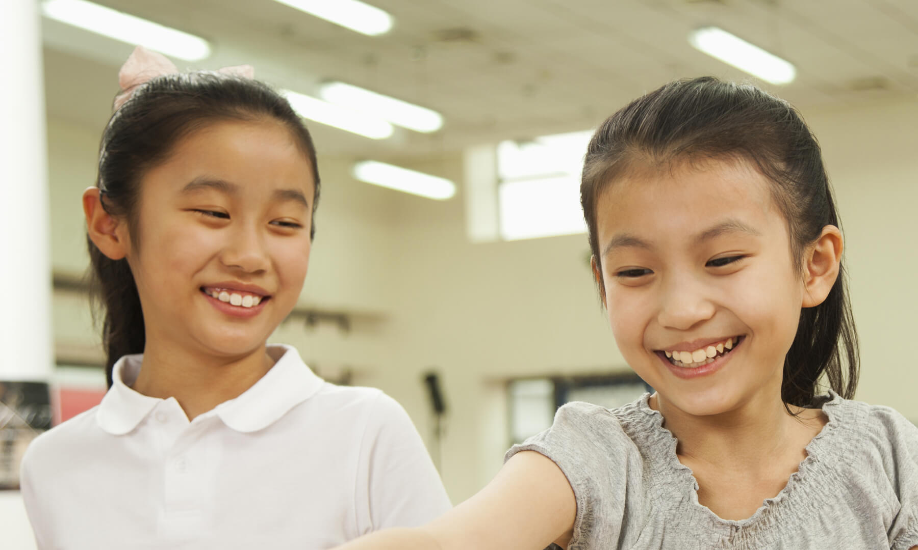 Two young Asian students smiling.