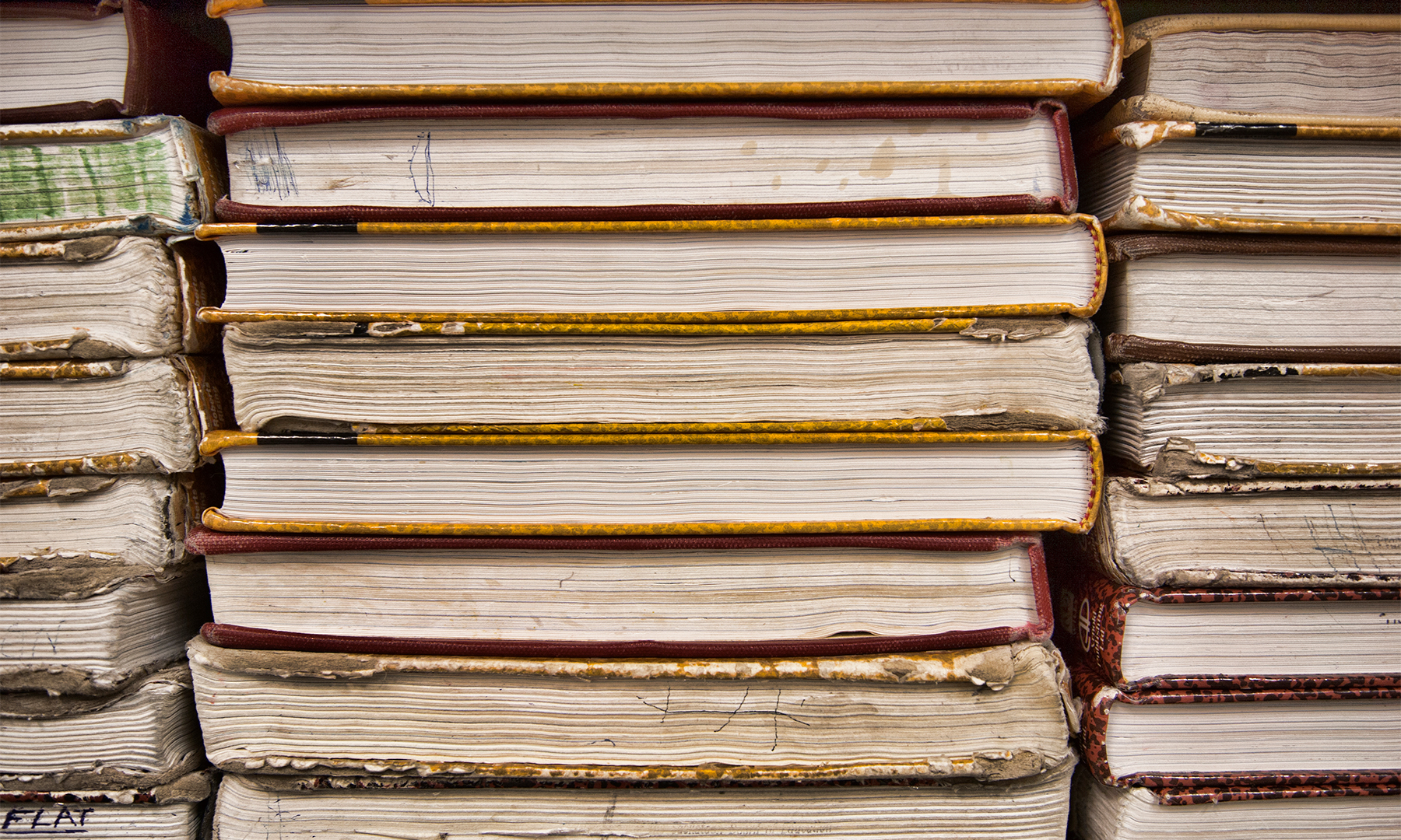 A stack of textbooks—viewed from the side—in varying conditions of use, from good to worn out.