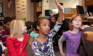 girl raising hand with peers in class