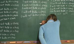"Child writing on the chalkboard ""I will not talk in class"""