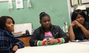 Three black students listen at a table