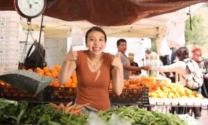 Positive woman in farmer's market
