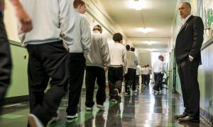 A teacher watches his students pass him in the hallways of a youth correctional facility