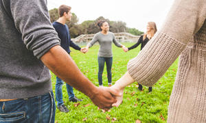 Young people stand in a circle holding hands