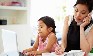 asian mother talking on phone with daughter on computer