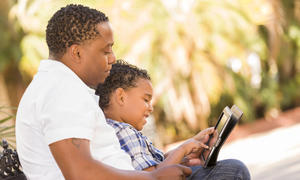 father and son looking at ipad outdoors
