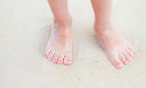 A child's bare feet are pictured standing on a beach
