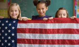 Three kids holding up American flag