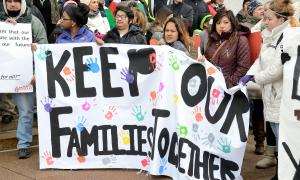 "Immigrant families and allies gather behind a sign that reads, ""Keep our families together."""