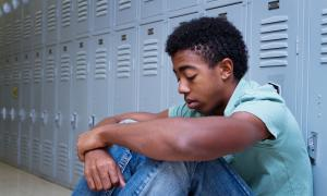 Sad African American student sitting against lockers | Hate at School May 2018