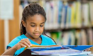 Young African-American girl reading books.