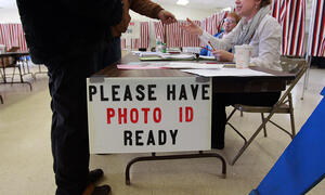 Voter handing photo identification to polling official.