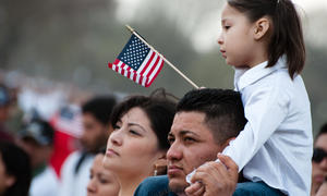 Young child holding American flag sitting on top of parent's shoulders.