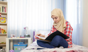 Young student in head wrap reading materials in their lap seated on a bed.