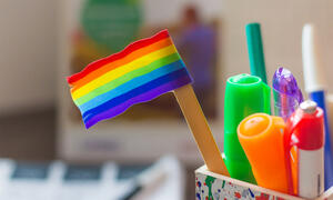 Small LGBTQ flag sitting in bin with writing utensils.