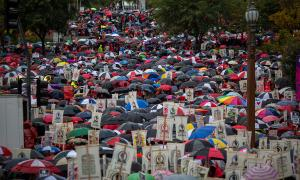 Hundreds of people gathered together, holding protest signs and umbrellas in Los Angeles, California.