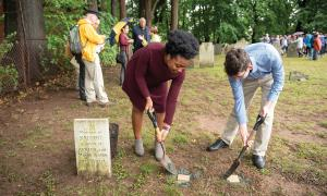 Two young people with spades digging near a burial marker.