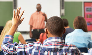 African-American student raising their hand in class, seen from behind.