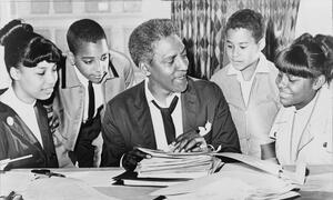 Civil rights and LGBTQ leader Bayard Rustin talking to four students gathered around him.