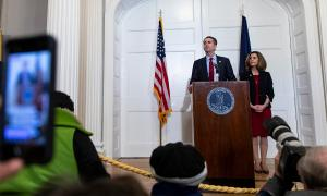 Ralph and Pam Northam behind a podium at a press conference.