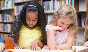 Two young students reading separate books.