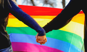 Two people holding hands in front of a rainbow flag.