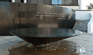 "Photograph of the Civil Rights Memorial wall and fountain. The words ""...until justice rolls down like waters and righteousness like a mighty stream. —Martin Luther King Jr."" appear plainly on the wall."