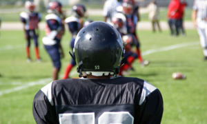 A football player in a uniform with their back to the viewer.