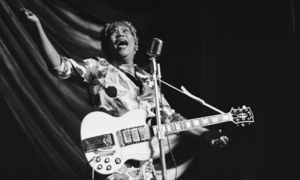Sister Rosetta Tharpe singing in front of a microphone.