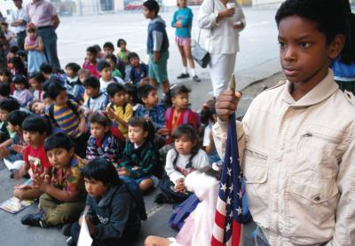 African American Student holding the US flag while younger students are sitting on the floor