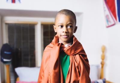 A kid standing on the bed with and adult shirt as a cape