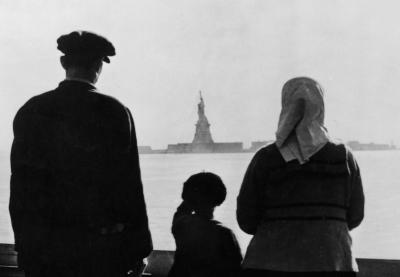 A couple of immigrants with their son look at the Statue of Liberty at distance