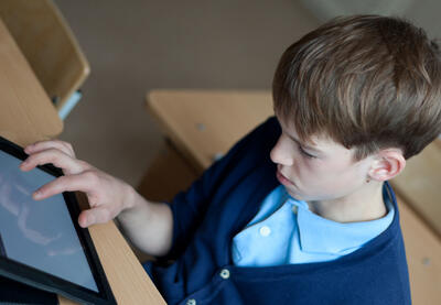 boy in school uniform looking at ipad
