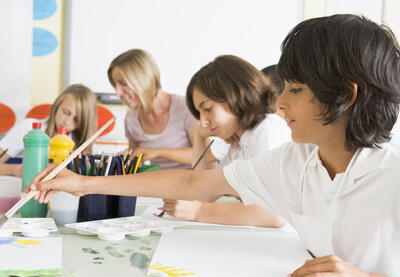 boy painting with classmates