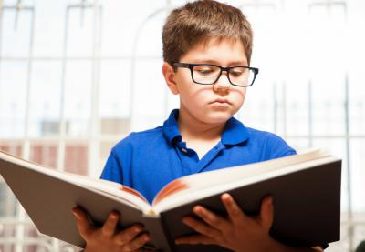 Boy in glasses reading a book