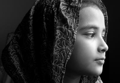 In a black and white photograph, a young girl wearing a head covering looks pensively off camera