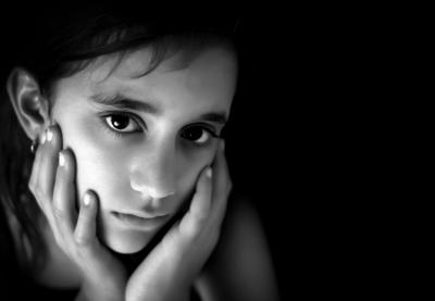 girl with face in hands looking sad in black and white