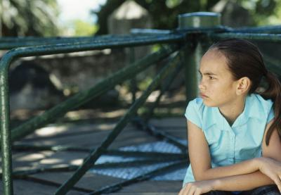 pensive determined youth of color leaning on playground