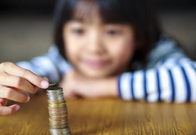 Asian girl stacking coins on table