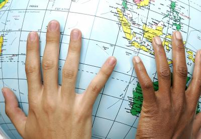 hands resting on globe