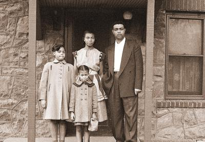 Historical photo of an African American family outside of a house