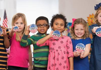 students holding vote buttons