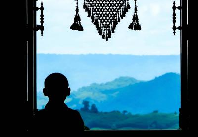 Child looking out onto the countryside, silhouetted in window