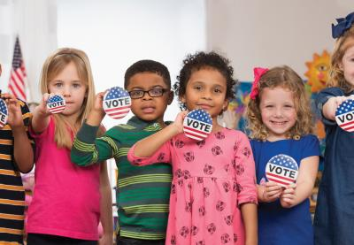 Young kids holding Vote buttons