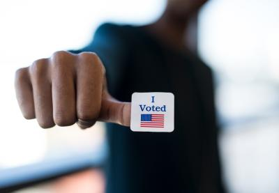 "Person with a ""I Voted"" sticker on their thumb"